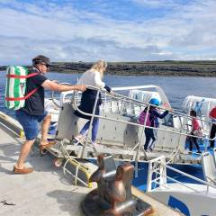 Passengers boarding Aran Islands Express ferry at Doolin Pier with Doolin Ferry Company.
